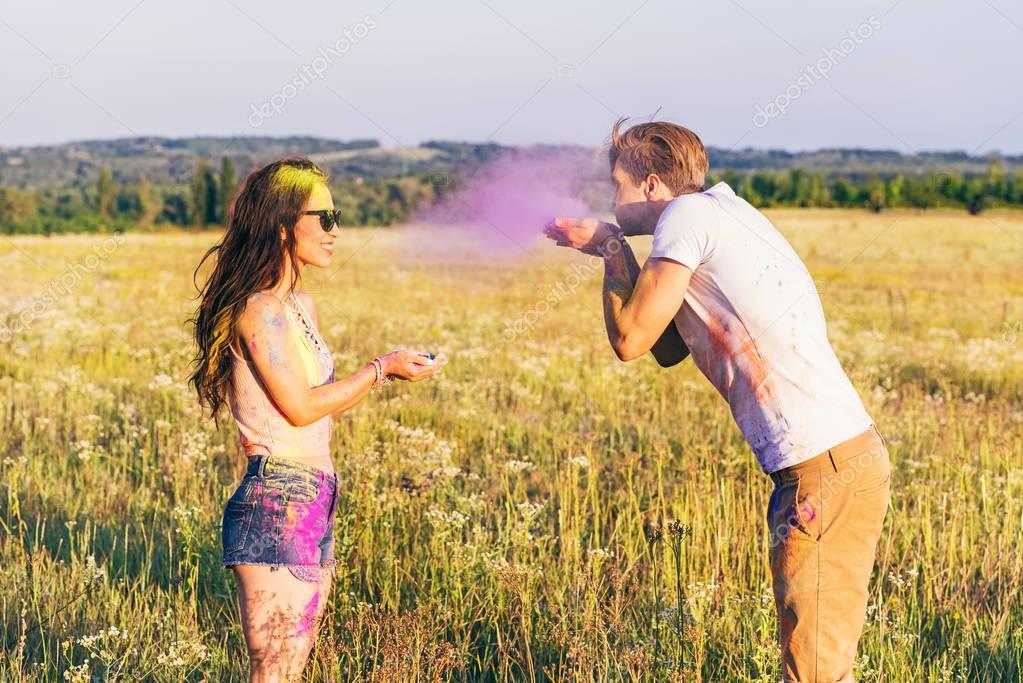 couple having fun during holi festival in field