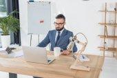 podnikatel, sedí na pracovišti s notebookem
