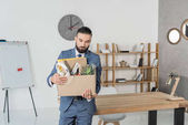fired upset businessman with cardboard box