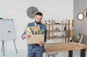fired upset businessman with cardboard box