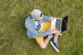 Muž s notebookem sedět na trávě