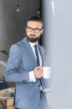 Side view of pensive businessman with coffee cup in hand looking away in office stock vector