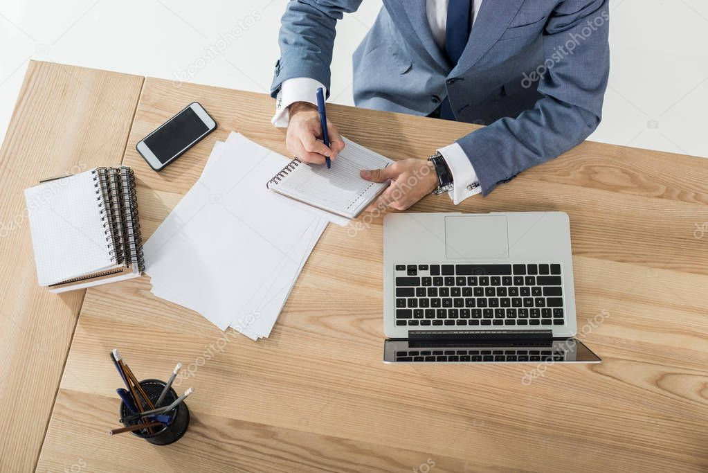 businessman writing in notebook at workplace