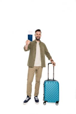Smiling man with suitcase holding passport and ticket in hand isolated on white stock vector