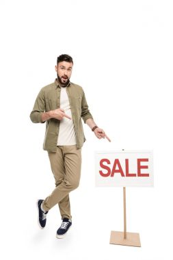 man pointing at sale sign