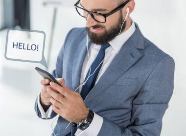 Businessman in earphones using smartphone
