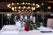 růžový květ s vínem u stolu v restauraci
