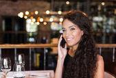 Frau telefoniert in Restaurant