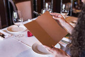 woman with menu in restaurant
