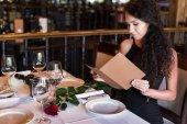Žena s menu v restauraci