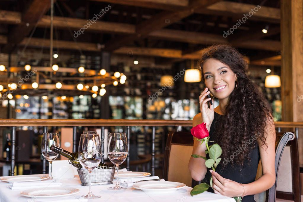 woman talking on phone in restaurant