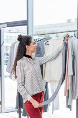woman choosing clothes in showroom