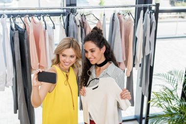 women taking selfie in clothes store