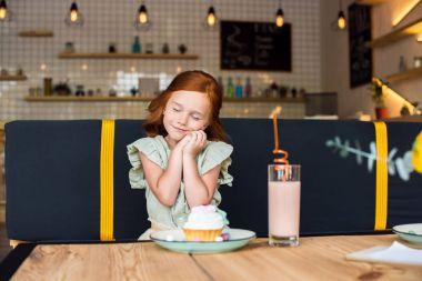 girl eating cupcake in cafe