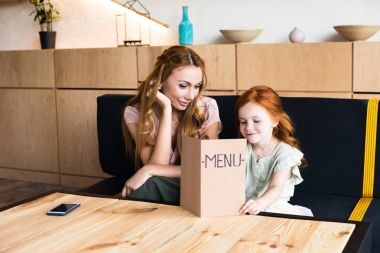 mother and daughter reading menu in cafe