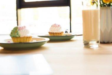 Milkshake and cupcakes on table