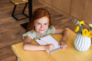 redhead girl drawing at table