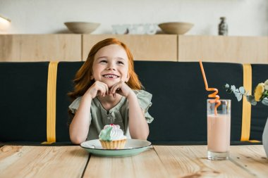 smiling girl with cupcake in cafe