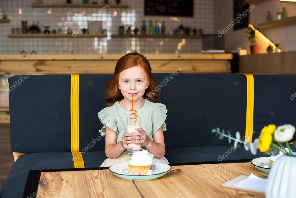 girl drinking milkshake in cafe