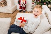 Fotografie Junge mit Weihnachtsgeschenk