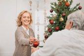 Fotografie muž a žena zdobí vánoční strom