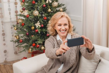 woman taking selfie with christmas tree