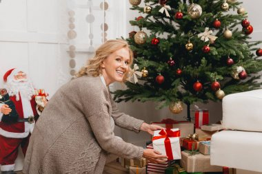 woman putting gifts under christmas tree