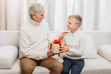 grandfather presenting christmas gift to grandson