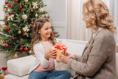 Mother presenting gift to daughter