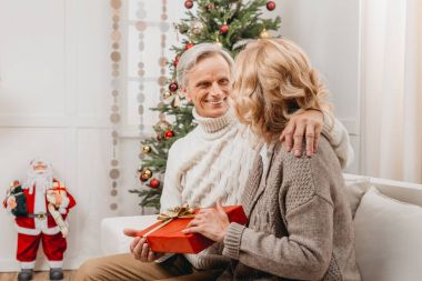 Smiling senior man presenting christmas gift to beautiful woman stock vector
