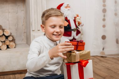 boy making stack of christmas gifts