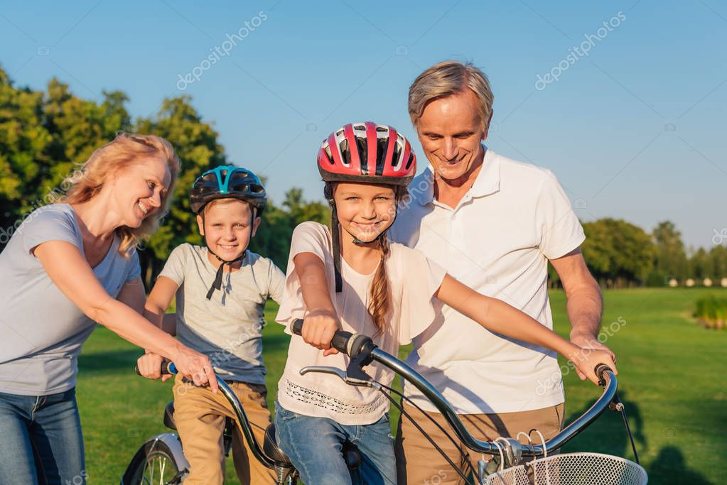 grandparents helping children ride bicycle