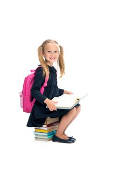 Happy schoolgirl sitting on stack of books isolated on white stock vector