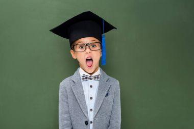 shocked schoolboy in graduation hat