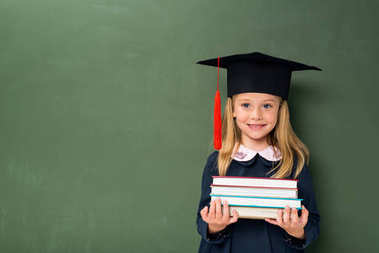 schoolgirl with stack of books and graduation hat
