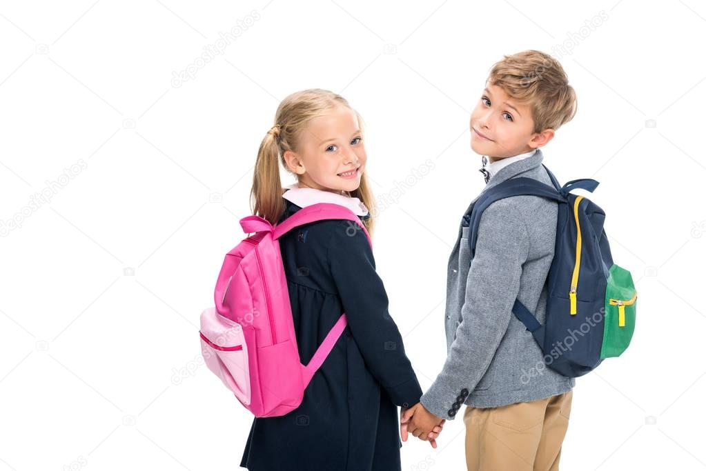 pupils with backpacks looking back