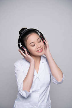 Half-length shot of smiling young woman in nurse outfit listening to music in big headphones. stock vector