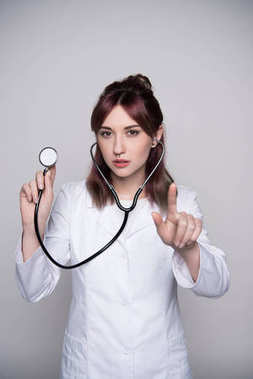Half-length shot of young female doctor in a white robe holding a stethoscope in her hand and pointing with her finger. stock vector
