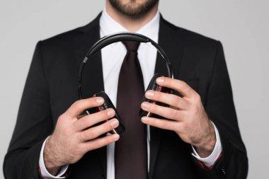 young businessman holding headphones in hands