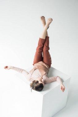stylish girl laying on white cube