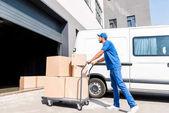 Fotografie Lieferung Mann mit Boxen auf Wagen