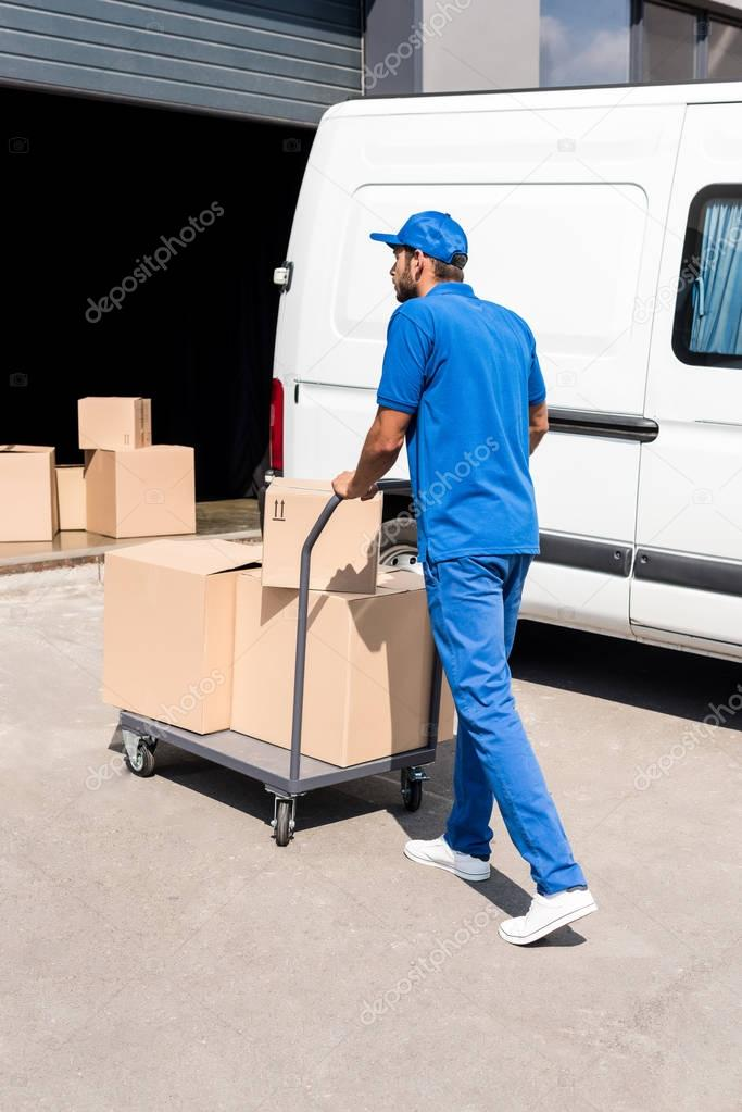 delivery man driving cart with boxes
