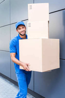 Happy delivery man with stack of cardboard boxes stock vector