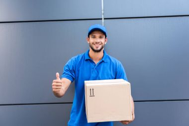 Delivery man with box showing thumb up stock vector