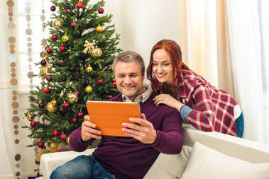 couple with digital tablet at christmastime