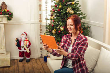 woman with gadget at christmastime