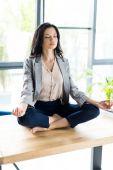 Geschäftsfrau meditiert am Arbeitsplatz