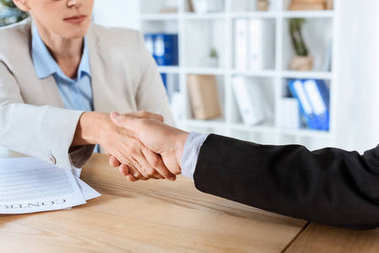 Cropped shot of business colleagues shaking hands stock vector