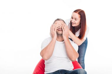 Woman closing eyes of husband