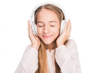 Happy teen girl listening music with headphones, isolated on white stock vector